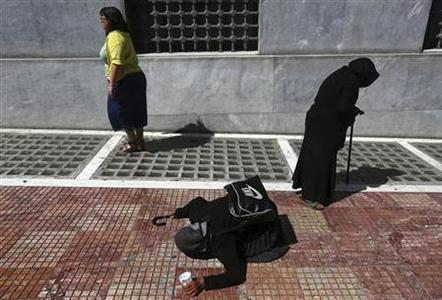 A woman walks by two foreign beggars outside the building of the Central Bank of Greece in central Athens May 16, 2012. REUTERS/Yannis Behrakis