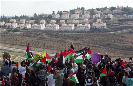 Palestinian and left-wing Israeli demonstrators rally during a weekly protest against a nearby Jewish settlement, seen in the background, in the West Bank village of Nabi Saleh, near Ramallah December 16, 2011. REUTERS/Darren Whiteside