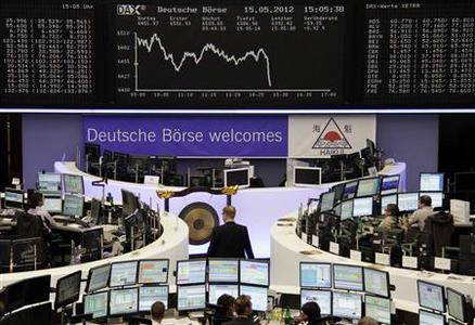 Traders work at their desks in front of the DAX board at the Frankfurt stock exchange. REUTERS/Remote/Kirill Iordansky