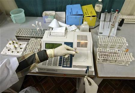 A laboratory assistant examines blood samples inside a laboratory in the northeastern Indian city of Siliguri November 2, 2006. REUTERS/Rupak De Chowdhuri