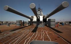 "Volunteers work under the 16-inch guns at the stern of the U.S. battleship ""USS Iowa"" in Richmond, California May 17, 2012. REUTERS/Robert Galbraith"
