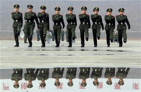Paramilitary recruits march during a training session as a banner in Chinese that reads ''Rigorous trainings, Strict requirements'' is reflected in a puddle at a military base in Nanjing, Jiangsu province March 6, 2012. REUTERS/China Daily