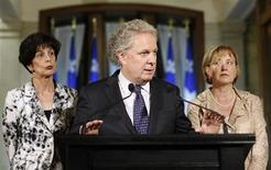 Quebec's Premier Jean Charest (C) and Minister of Education Michelle Courchesne (L) speak during a news conference at the National Assembly in Quebec City, May 16, 2012. REUTERS/Mathieu Belanger