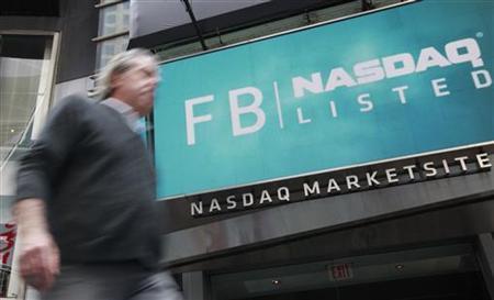 A man walks past a sign welcoming Facebook to the NASDAQ Marketsite in New York May 18, 2012. REUTERS/Brendan McDermid