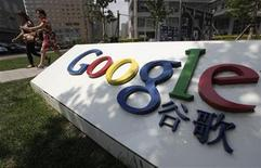 Women walk past the logo of Google in front of its former headquarters, in Beijing June 2, 2011. REUTERS/Jason Lee