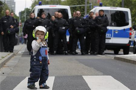 A child stands in front of German riot police officers during an anti-austerity demonstration in Frankfurt May 19, 2012. REUTERS/Alex Domanski