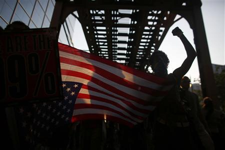 Protesters holding an American flag march over a bridge during an anti-NATO protest march in Chicago May 19, 2012. REUTERS/ Darren Hauck