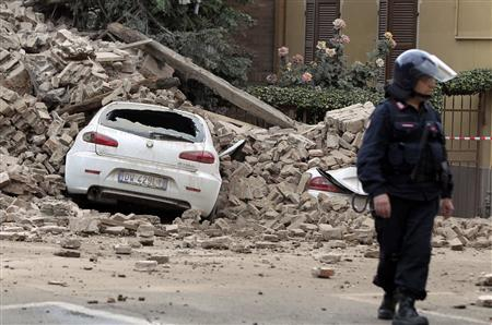 A Carabinieri paramilitary officer stands near a damaged car after a strong aftershock struck Finale Emilia May 20, 2012. REUTERS/Giorgio Benvenuti