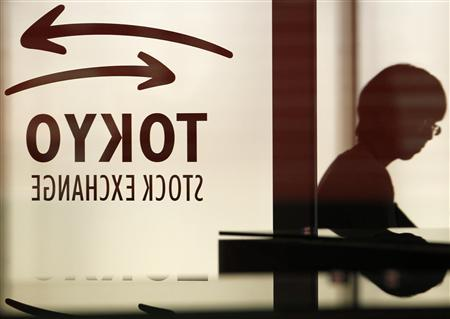 A woman walks past a logo of Tokyo Stock Exchange at the bourse in Tokyo May 18, 2012. REUTERS/Yuriko Nakao