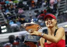 Теннисистка Мария Шарапова держит кубок теннисного турнира в Риме, 20 мая 2012 года. Российская теннисистка Мария Шарапова сломила в воскресенье сопротивление китаянки Ли На и стала победительницей турнира в Риме второй год подряд. REUTERS/Alessandro Bianchi
