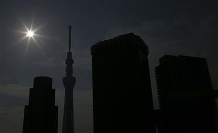 An eclipse is seen over Tokyo Sky Tree (2nd L) which is the world's tallest free-standing broadcast tower in Tokyo May 21, 2012. REUTERS/Kim Kyung-Hoon