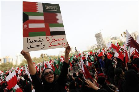 A pro-government protester holds up a placard showing GCC flags that reads: ''One Union One Youth'' as she shouts pro-government slogans in a rally to show support towards GCC Union, in al Fateh Grand Mosque in Manama, May 19, 2012. REUTERS/Hamad I Mohammed
