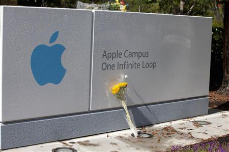A bouquet of flowers in honor of the passing of former Apple CEO Steve Jobs lies in front of the sign of Apple headquarters in Cupertino, California October 6, 2011. REUTERS/Norbert von der Groeben