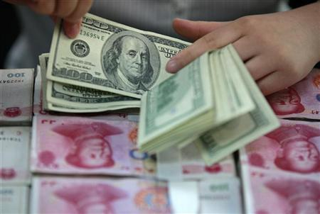 A bank clerk counts U.S. dollar banknotes on bundles of 100 Chinese yuan banknotes at a branch of a bank in Huaibei, Anhui province April 26, 2012. REUTERS/Stringer