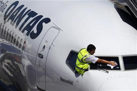 A ground crew member cleans the windshield of a Qantas passenger plane at Adelaide airport in this February 13, 2012 file photo. REUTERS/Tim Wimborne/Files