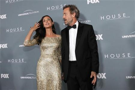 Cast member Hugh Laurie (R) poses with co-star Odette Annable at the series finale wrap party of the television series ''House M.D.'' in Los Angeles, California April 20, 2012. REUTERS/Mario Anzuoni