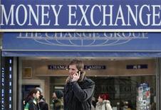 Мужчина говорит по мобильному телефону около пункта обмена валют в Вене, 14 февраля 2012 года. Восстановление евро с четырехмесячных минимумов прекратилось во вторник, так как валюта не смогла преодолеть техническое сопротивление. REUTERS/Heinz-Peter Bader