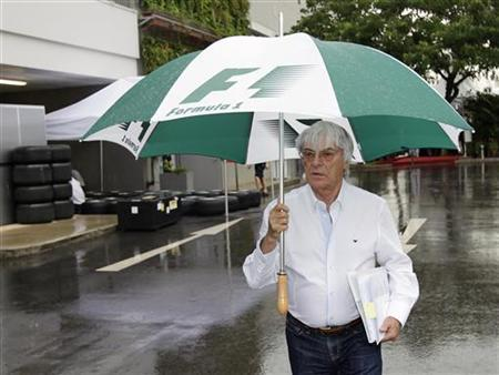 Formula One commercial supremo Bernie Ecclestone holds an umbrella as he arrives in the rain at the Singapore F1 Grand Prix at the Marina Bay circuit September 23, 2010. REUTERS/Tim Chong
