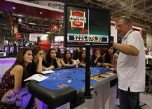 Attendants learn a poker game before introducing them to visitors at Gaming Expo Asia in Macau May 22, 2012. REUTERS/Bobby Yip