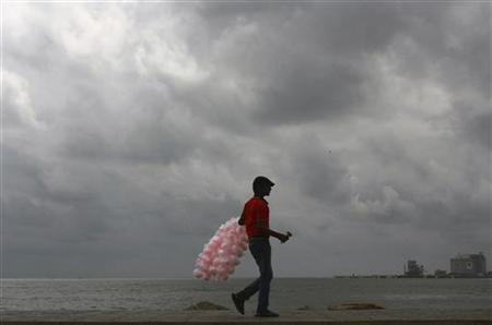 A vendor selling candy floss walks on a seaside promenade as monsoon clouds gather over the sea in Kochi April 25, 2012. REUTERS/Sivaram V/Files