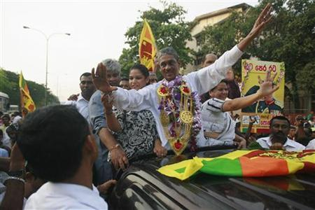Ex-General Sarath Fonseka waves at his supporters as he leaves the Welikada prison in Colombo May 21, 2012. REUTERS/Dinuka Liyanawatte