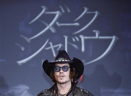 Actor Johnny Depp poses in front of a screen showing the name of the film in Japanese during a photo call at a news conference for their film ''Dark Shadows'' in Tokyo May 13, 2012. REUTERS/Yuriko Nakao