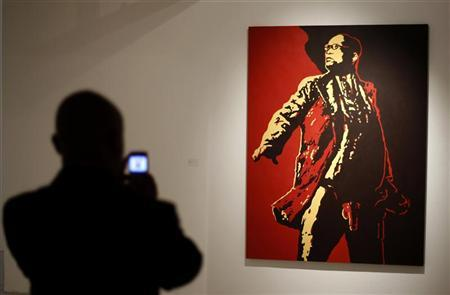 A visitor photographs a painting of South Africa's President Jacob Zuma at an exhibition in Johannesburg May 18, 2012. REUTERS/Siphiwe Sibeko