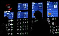 Visitors look at monitors displaying market indices at the Tokyo Stock Exchange in Tokyo May 18, 2012. REUTERS/Yuriko Nakao