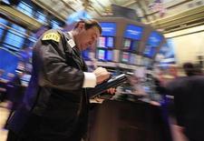 Трейдеры на Нью-Йоркской фондовой бирже, 20 января 2012 года. Американский фондовый рынок закрылся практически без изменений на торгах вторника после волатильного конца торговой сессии из-за слабых результатов секторов энергетики и материалов, затмивших хорошие результаты финансового сектора. REUTERS/Brendan McDermid