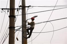 Рабочий проверяет исправность линий электропередачи в центре Пекина 18 мая 2012 года. Китай сообщил в среду о намерении повысить инвестиции в энергетический сектор наряду с планами ускорения инфраструктурных инвестиций, чтобы побороть замедление экономики. REUTERS/David Gray