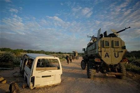 An African Union Mission in Somalia (AMISOM) armoured personnel carrier moves along a road past a destroyed vehicle during a joint AMISOM and Somali National Army (SNA) operation against Al-Shabaab militants in Deyniile May 22, 2012. REUTERS/Stuart Price/African Union-United Nations Information Support Team/Handout