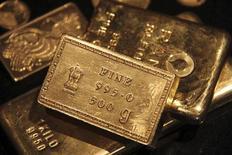 Золотые слитки в ювелирном магазине в индийском городе Чандигарх, 11 апреля 2012 года. Цены на золото снижаются из-за опасений, что саммит Евросоюза в среду не избавит рынки от страха перед долговым кризисом еврозоны. REUTERS/Ajay Verma