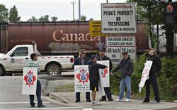 Picketers stand at the entrance to the CP Rail yards in Coquitlam, British Columbia May 23, 2012. Locomotive engineers and conductors at Canadian Pacific Railway walked off the job on Wednesday after contract talks broke down, shutting down freight operations on Canada's second-biggest railroad. REUTERS/Andy Clark