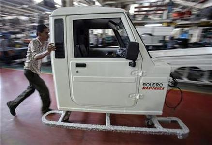 An employee pushes the frame of the cabin of a Mahindra Bolero vehicle at the company's manufacturing plant on the outskirts of Mumbai May 23, 2012. REUTERS/Vivek Prakash