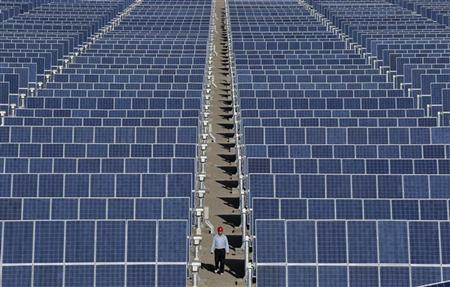 An employee walks between rows of solar panels at a solar power plant on the outskirts of Dunhuang, Gansu province June 10, 2011. REUTERS/Stringer