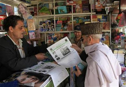 A man buys Ensaf newspaper at a kiosk in Kabul May 22, 2012. REUTERS/Mohammad Ismail
