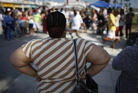 An overweight woman watches a street performer at Venice Beach in Los Angeles, California, May 11, 2012. REUTERS/David McNew