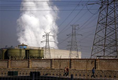 Pedestrians walk along a footpath in front of a massive chimney billowing smoke for a coal-burning power station in central Beijing January 12, 2012. REUTERS/David Gray