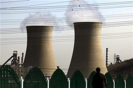 A man looks over a fence towards chimneys of a coal-burning power station located on the outskirts of Beijing November 22, 2011. REUTERS/David Gray/Files