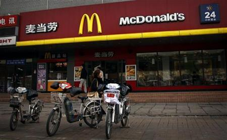 A woman walks past electric bikes sitting outside a McDonalds fast-food outlet in central Beijing March 20, 2012. REUTERS/David Gray/Files