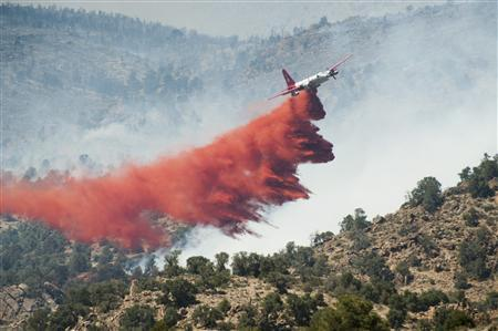 A Cal Fire aircraft drops flame retardant on the Topaz Ranch Estates Fire in Wellington, Nevada May 23, 2012. Evacuations were lifted today as the fire moved north into the canyons. REUTERS/James Glover