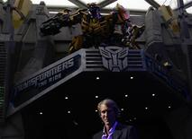 """U.S. film director and producer Michael Bay poses below a model of the Bumblebee Autobot character at the premiere launch for the """"Transformers-The Ride"""" at Universal Studios Singapore theme park, part of Resorts World Sentosa in Singapore December 2, 2011. REUTERS/Tim Chong"""