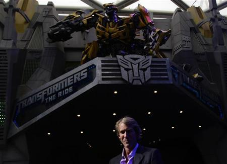 U.S. film director and producer Michael Bay poses below a model of the Bumblebee Autobot character at the premiere launch for the ''Transformers-The Ride'' at Universal Studios Singapore theme park, part of Resorts World Sentosa in Singapore December 2, 2011. REUTERS/Tim Chong