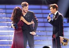 "Phillip Phillips is hugged by Jessica Sanchez after he was named the winner by host Ryan Seacrest (R) during the 11th season finale of ""American Idol"" in Los Angeles, California May 23, 2012. REUTERS/Mario Anzuoni"