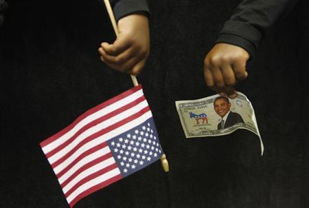 A supporter of U.S. Democratic presidential nominee Senator Barack Obama (D-IL) holds a fake bill with Obama's face at a campaign rally in Fayetteville, North Carolina, October 19, 2008. REUTERS/Jim Young
