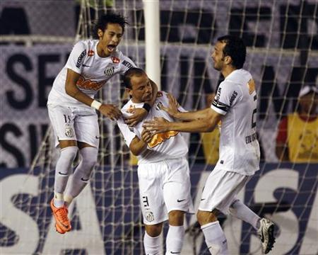 Neymar (L), Leo (C) and Edu Dracena of Brazil's Santos celebrate beating Argentina's Velez Sarsfield in a penalty shootout during their quarter-final Copa Libertadores soccer match in Santos, May 24, 2012. REUTERS/Paulo Whitaker