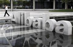 Мужчина проходит мимо логотипа Alibaba Technology Co. Ltd около здания офиса компании в Ханчжоу (КНР), 11 августа 2011 года. Инвестиционный фонд China Investment Corp (CIC) ведет переговоры о покупке на сумму до $2 миллиардов пакета акций китайской интернет-компании Alibaba Group, сообщили источники Рейтер. REUTERS/Steven Shi