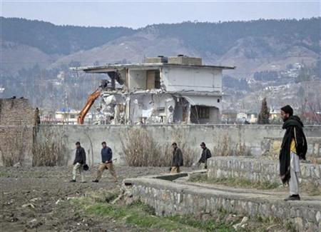 Policemen walk past while demolition work is carried out on the building where al Qaeda leader Osama bin Laden was killed by U.S. special forces last May, in Abbottabad February 26, 2012. REUTERS/Sultan Dogar