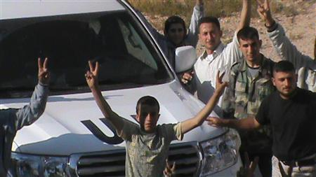People gesture around a convoy of United Nations observers on a monitoring mission in Syria upon their arrival in Rasten, near Homs May 20, 2012. REUTERS/Shaam News Network/Handout