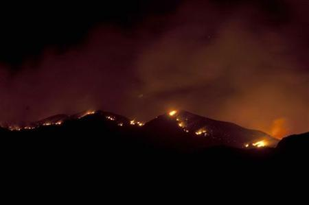 A view of the Gladiator Fire near Crown King, Arizona as shown from the fire operations base camp at Mayer High School in Mayer, Arizona May 15, 2012 in this photo obtained by Reuters May 20, 2012. Fires in Arizona, New Mexico and Colorado have forced the evacuation of several small towns and torched more than 65 square miles (168 square km) of forest, brush and grass in the U.S. Southwest. After getting a respite from winds on Saturday, firefighters on the Gladiator Fire faced a combination of dry vegetation and higher winds on Sunday and the days ahead. Picture taken May 15, 2012. REUTERS-Todd Tamcsin